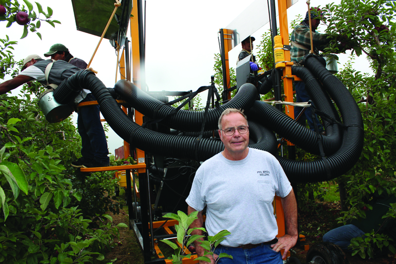 Phil Brown poses in front of his invention, the Apple Harvester, while workers use it to pick apples in an orchard.