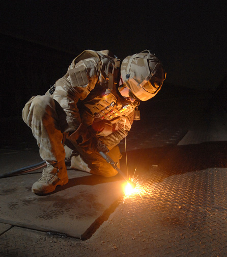 A soldier uses the oxyacetylene welding process on a construction project in Iraq.