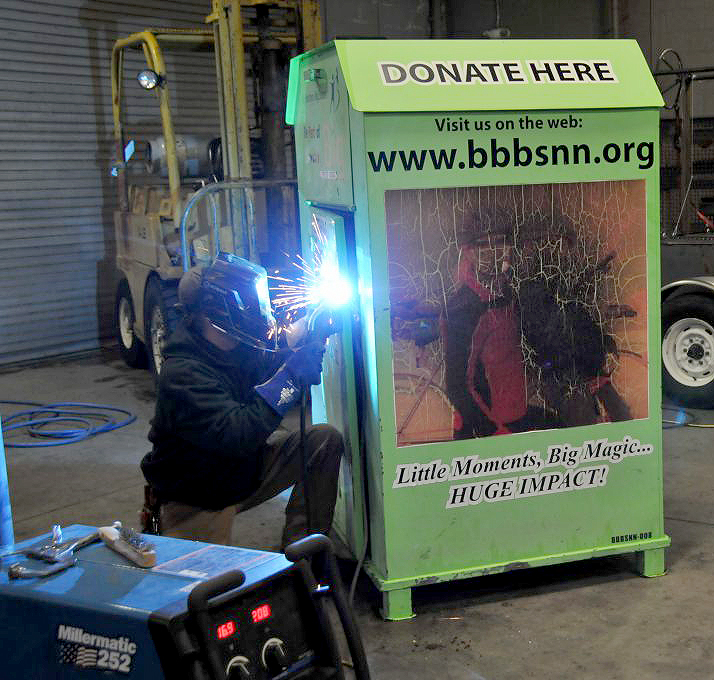 A student welder from Western Nevada College repairs a vandalized donation bin..