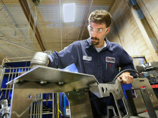 Welder apprentice, Jake Ritchie, smooths the edges of an aluminum weldment at GenMet Corp.